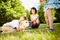 Le garçon caresse avec le golden retriever images libres de droits