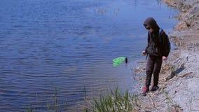 Le garçon cathcing des grenouilles et des poissons sur la rivière utilisant le filet de papillon banque de vidéos