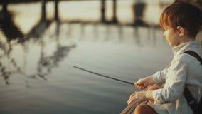 Le garçon caucasien adorable joue avec le bâton près du lac Petit enfant mignon avec le sac à dos sur un pilier Enfance heureux 4 clips vidéos