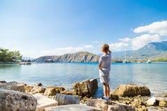 Le garçon caucasien dans un T-shirt blanc et des shorts blancs coûte par la mer à terre pendant l'après-midi d'été et regarde b images libres de droits