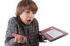 Le garçon choqué avec son PC de comprimé a entaillé par un virus de ransomware image libre de droits