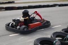 Le garçon conduit la voiture de kart avec la vitesse dans une voie d'emballage de terrain de jeu photo libre de droits
