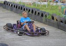 Le garçon conduit un kart sur le circuit images libres de droits