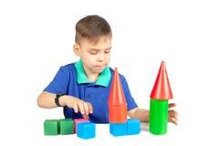 Le garçon construit une maison des cubes photos stock