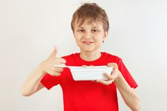 Le garçon coupé peu dans une chemise rouge recommande les nouilles instantanées sur le fond blanc image libre de droits