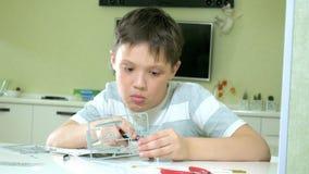 Le garçon crée un avion modèle en plastique, une copie précise, du concepteur banque de vidéos