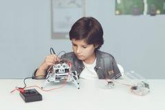 Le garçon crée un robot Il mesure ses données avec un multimètre Le garçon observe les mesures Images stock