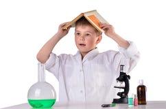 Le garçon déconcertant de scientifique avec le livre sur le sien a eu sur le fond blanc photo stock