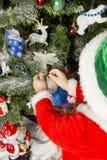 Le garçon décore un arbre de Noël Photo stock