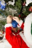 Le garçon décore un arbre de Noël Photographie stock