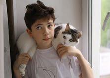 Le garçon d'adolescent avec le chat sur ses épaules se ferment vers le haut de la photo Photos stock