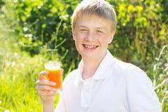 Le garçon d'adolescent juge de verre avec du jus de carotte images stock