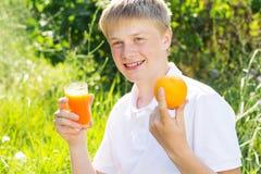 Le garçon d'adolescent juge de verre avec du jus de carotte Photos stock