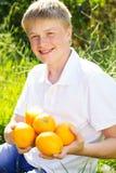 Le garçon d'adolescent juge de verre avec le jus d'orange Photographie stock libre de droits