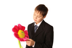 Le garçon d'adolescent regarde une fleur de jouet Image stock