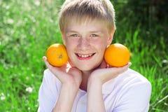 Le garçon d'adolescent tient deux oranges Photographie stock libre de droits
