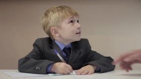 Le garçon d'aide de professeur écrivent clips vidéos