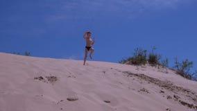 Le garçon d'enfant court des chutes de sauts de la dune de sable énorme sur la plage de mer dans des vacances d'été clips vidéos