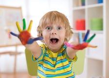 Le garçon d'enfant dessine avec des mains et montre les paumes peintes multicolores Jeux éducatifs du ` s d'enfants avec des pein images stock