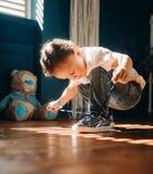 Le garçon d'enfant en bas âge apprend à attacher les dentelles sur ses espadrilles photo libre de droits