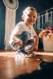 Le garçon d'enfant en bas âge apprend à attacher les dentelles sur ses espadrilles images stock