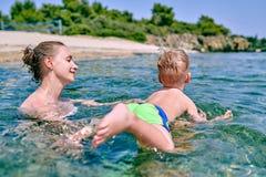 Le garçon d'enfant en bas âge apprend à nager avec la mère photographie stock libre de droits