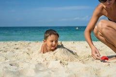 Le garçon d'enfant en bas âge de quatre ans jouant avec la plage joue avec la mère dessus Photos libres de droits
