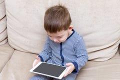 Le garçon d'enfant en bas âge utilise un comprimé sur un divan image libre de droits