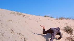 Le garçon d'enfant est roulant et dégringolant en bas des dunes de sable sur la plage de mer aux vacances banque de vidéos