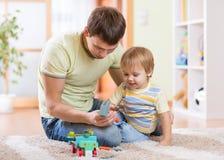 Le garçon d'enfant et son père réparent la voiture de jouet à la maison Image libre de droits