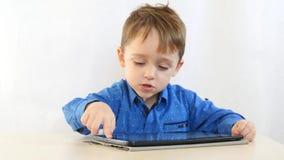 Le garçon d'enfant s'assied à une table et joue avec ses mains avec des pièces de monnaie, sur un fond blanc banque de vidéos