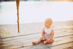Le garçon d'enfant un an de blond s'assied sur un dock en bois, un pilier dans des vêtements rayés, un composé près de l'étang su Photo stock