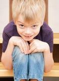 Le garçon d'une manière amusante s'assied sur une échelle Images stock