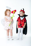 Le garçon dans l'image du diable et d'un ange de fille Photographie stock libre de droits