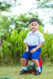Le garçon dans l'uniforme thaïlandais d'étudiant et le sac à dos pour vont à l'école Photographie stock libre de droits