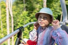 Le garçon dans la chaise du funiculaire de montagne image libre de droits