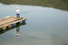 Le garçon dans la chemise blanche et le chapeau se tenant sur Pier With en bois Rod And Patiently Waiting To de pêche pêchent un  Photos stock