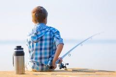 Le garçon dans la chemise bleue s'asseyent sur un tarte Image stock