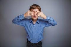 Le garçon dans la chemise observe les mains fermées sur le fond gris Image libre de droits