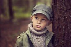 Le garçon dans la forêt se penche contre un tronc d'arbre images stock