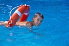Le garçon dans la piscine avec une ligne de sauvetage Photo stock