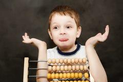 Le garçon dans la surprise a répandu ses bras près de l'abaque en bois Photographie stock