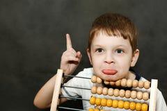 Le garçon dans la surprise a répandu ses bras près de l'abaque en bois Photo libre de droits