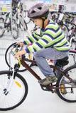 Le garçon dans le casque s'assied sur la bicyclette et regarde vers le bas Photo libre de droits