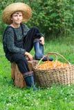 Le garçon dans le chapeau de paille s'assied avec le panier des chanterelles Photographie stock libre de droits