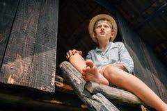 Le garçon dans le chapeau de paille s'assied sur le chef en bois à la grange Photo stock