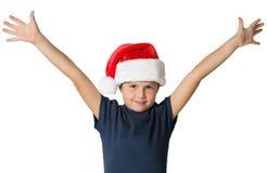 Le garçon dans le chapeau rouge de Santa Claus sourit gaiement Photographie stock