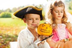 Le garçon dans le costume du pirate ouvre le potiron de Halloween Image stock