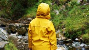 Le garçon dans le manteau jaune observe la rivière Photos stock