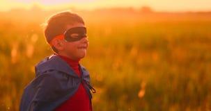 Le garçon dans le masque et le cap d'un superhéros au coucher du soleil dans un domaine banque de vidéos